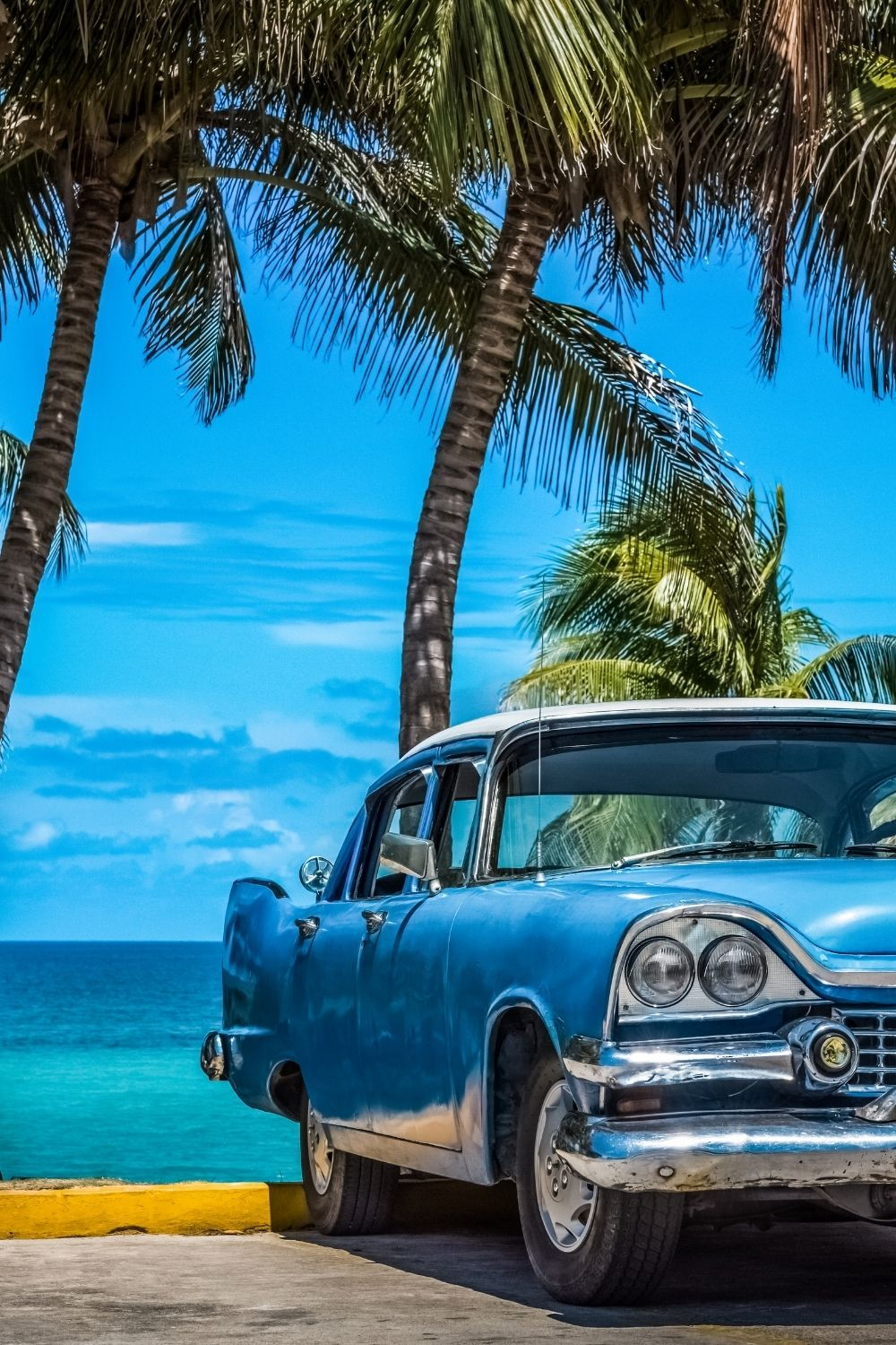 blue shiny cadillac infront of the beach and a few visible palm trees, this image was taken in cuba